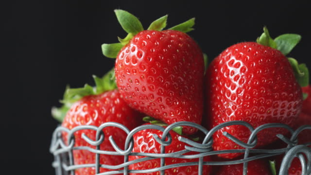 macro shot of organic, juicy strawberries against black background - juicy stock videos & royalty-free footage
