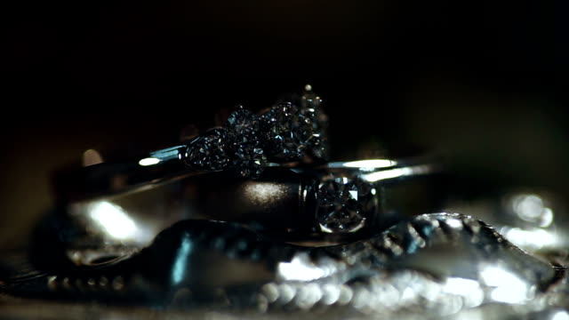 macro shot of wedding rings on silver background. - ring stock videos and b-roll footage