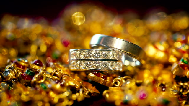 vídeos de stock e filmes b-roll de macro shot of wedding rings with golden background. - anel joia