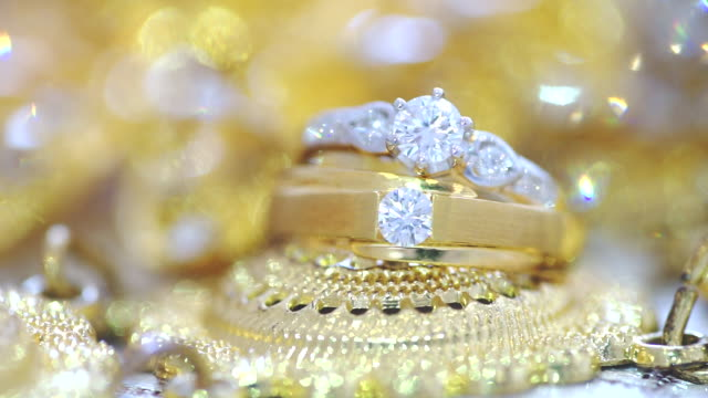 macro shot of wedding rings with golden textured background. - wedding ring stock videos & royalty-free footage