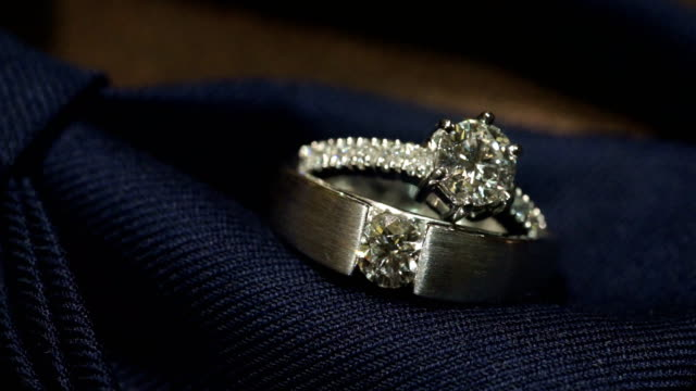 macro shot of wedding rings with textured background. - ring stock videos and b-roll footage