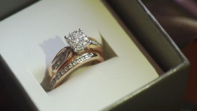 テクスチャの背景を持つ結婚式のリングのマクロショット。結婚式のテーマ。 - 結婚指輪点の映像素材/bロール