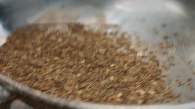 macro shot sprinkling and frying cumin in a pan. - spice stock videos & royalty-free footage