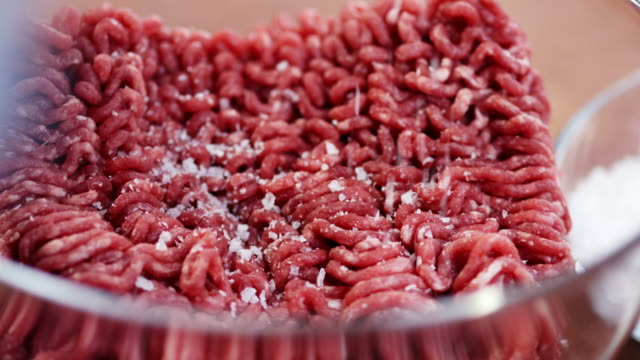macro shot sprinkling salt on beef mince. - spice stock videos & royalty-free footage