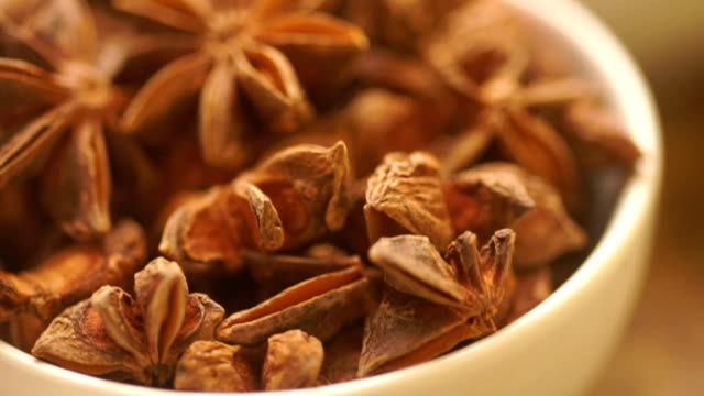 macro shot : star anise in a white bowl on a wooden table. - star anise stock videos and b-roll footage