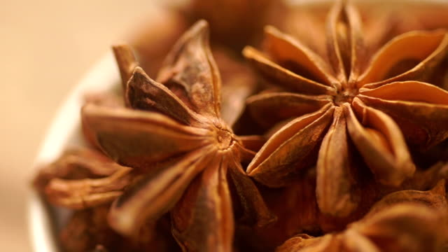 macro shot : star anise in a white bowl. - star anise stock videos and b-roll footage
