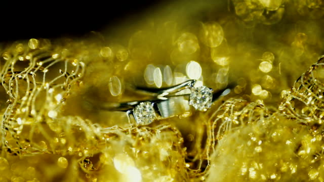 Macro shot Wedding rings with golden textured background. Wedding theme.