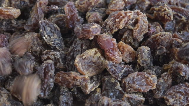 stockvideo's en b-roll-footage met macro slow motion of raisins falling over a pile - rozijn