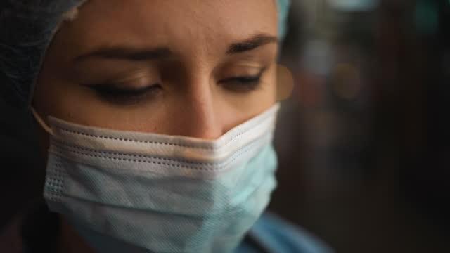 vídeos de stock e filmes b-roll de macro: very sad female doctor or nurse feeling down at night - bata cirúrgica