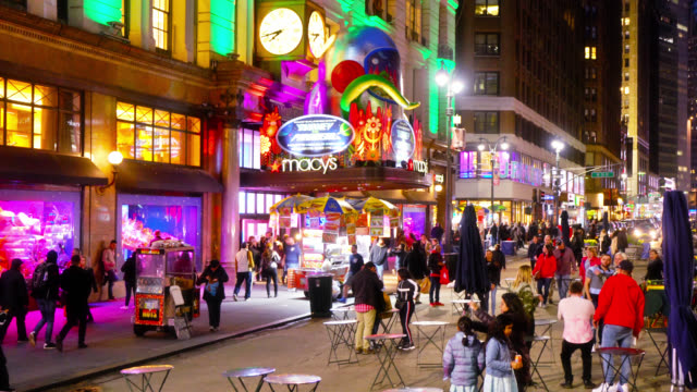 macy's store and other retail and consumer shops on a crowded street. new yorkers looking at teh illumination. lit up windows. new york, us - editorial stock videos & royalty-free footage