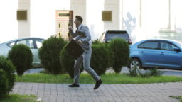 Mad businessman or lawyer with a briefcase is dancing in the city.