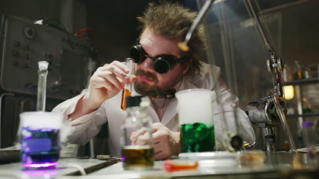 Mad scientist drinking liquid in laboratory then choking / Cedar Hills, Utah, United States