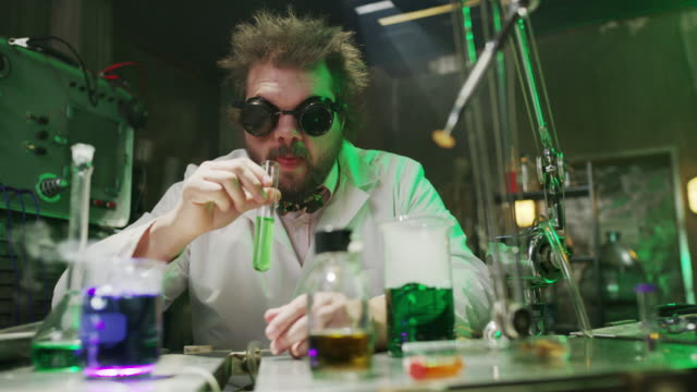 vídeos de stock e filmes b-roll de mad scientist drinking liquid in laboratory then laughing / cedar hills, utah, united states - óculos de proteção