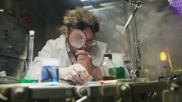 mad scientist examining test tubes with magnifying glass in laboratory / cedar hills, utah, united states - lupe stock-videos und b-roll-filmmaterial