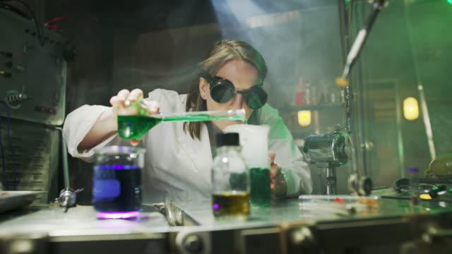 mad scientist mixing liquid in laboratory then checking syringe / cedar hills, utah, united states - becher video stock e b–roll