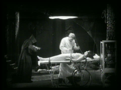 b/w mad scientist preparing to experiment on woman strapped to table - scientific experiment stock videos & royalty-free footage