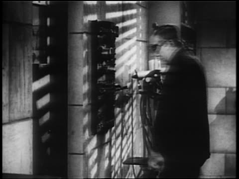 b/w 1940 mad scientist puts on goggles flips levers looks at flashing lights thru window - lever stock videos & royalty-free footage