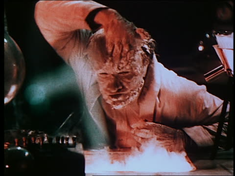 vídeos de stock e filmes b-roll de mad scientist spreading synthetic flesh on his face + becoming a monster in laboratory - só um rapaz