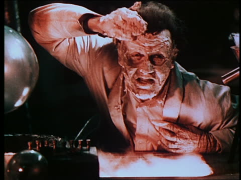 mad scientist spreading synthetic flesh onto his face + becoming a monster in laboratory - stage make up stock videos and b-roll footage