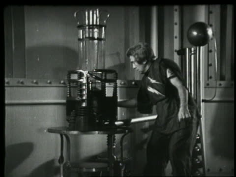 B/W 1935 mad scientist (Billy Bletcher) with thunderbolt shirt operating bizarre machine