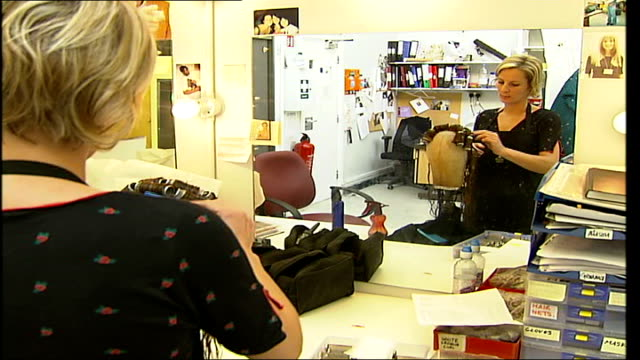 madame tussauds waxworks / workshop madame tussauds employee working on wig of waxwork figure close up of hair combed new follicles inserted /... - madame tussauds stock videos & royalty-free footage