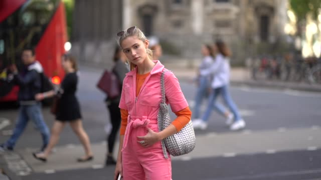 maddie close wears a pink corduroy jumpsuit a knitted belt a silver metallic bag brown platform shoes an orange top sunglasses over the head a ring... - jumpsuit stock videos & royalty-free footage
