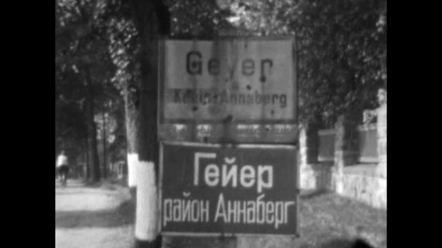 made between 1951 and 1953 steam train passes 1930's era car drives over bridge city limit sign of geyer in the county of annaberg erzgebirge in... - 1930 stock-videos und b-roll-filmmaterial