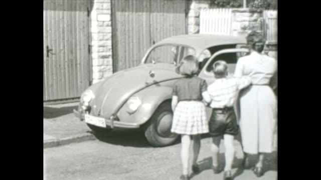made in the 1950s family presenting their new car their first VW Beetle / VW Käfer to the camera everyone from child to grandmother is shown while...