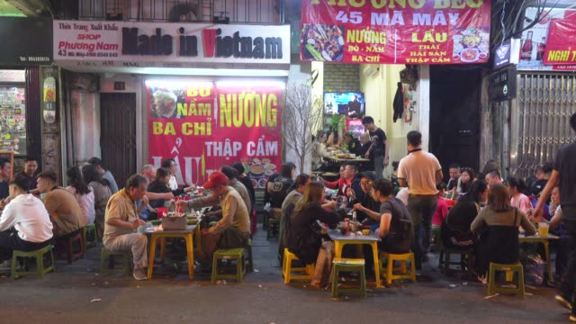 made in vietnam banner above vietnamese people eating at restaurant terrace during tet. hanoi old quarter nightlife. hoan kiem old town district - traditionally vietnamese stock videos & royalty-free footage