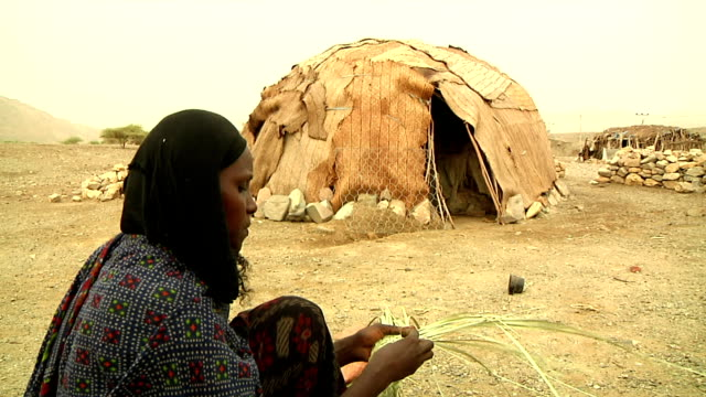 made of wood and straw ethiopian woman braiding straw next to hut on august 13, 2011 in afar village, danakil depression, ethiopia - ethiopia stock videos & royalty-free footage