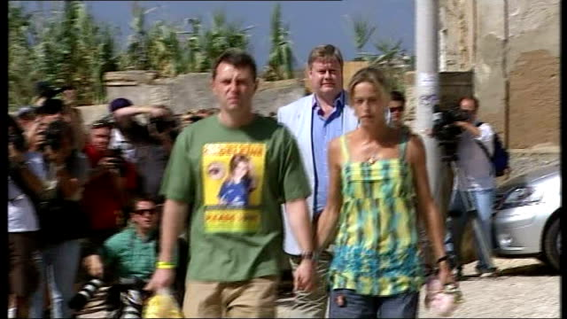 100 days PORTUGAL Algarve Praia da Luz EXT Gerry McCann and Kate McCann along past onlookers and press and into church Close Shot Poster cards and...