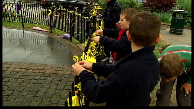 description of suspect england leicestershire rothley ext children tying on yellow ribbons to railings - レスターシャー点の映像素材/bロール