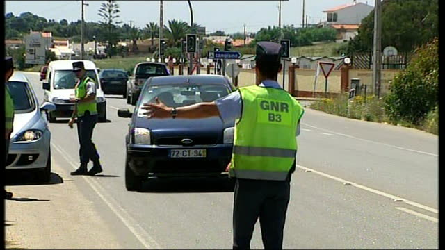 madeleine mccann abduction: description of suspect; police flagging down and chatting to motorists - vermißte person stock-videos und b-roll-filmmaterial