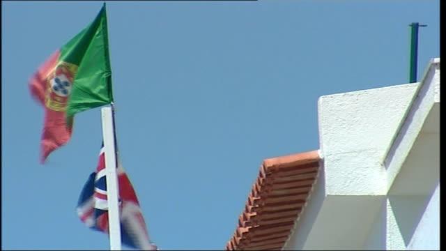 madeleine mccann abduction: description of suspect; portuguese flag and united kingdom flag blowing in wind on flagpole people along on street - マデリン・マクカーン失踪事件点の映像素材/bロール