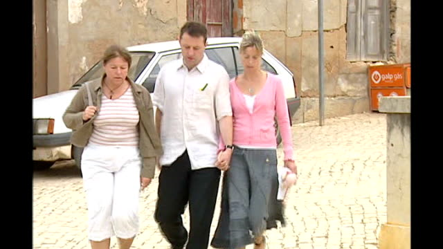 father flies back to Britain PORTUGAL The Algarve Praia da Luz EXT Gerry McCann Kate McCann walking along street with another