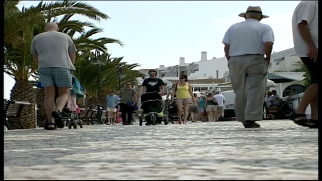madeleine mccann abduction: investigation update; praia da luz: ext people to and fro along street - algarve stock-videos und b-roll-filmmaterial