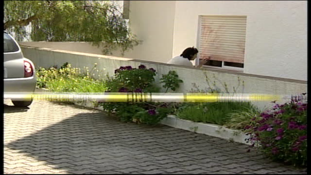 Investigation update TX PORTUGAL The Algarve Praia da Luz EXT Back View Police forensic officer collecting evidence from shutters in holiday...
