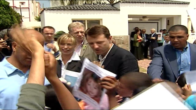 madeleine's parents meet with government officials morocco ext gerry mccann and kate mccann along thru crowd of children all holding up posters of... - madeleine mccann video stock e b–roll