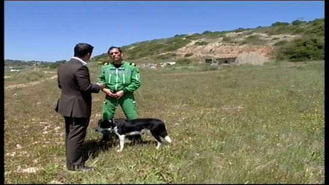 mother makes appeal portuguese police officers searching fields near holiday resort simmons chatting to officer officer searching field hotel complex... - madeleine mccann video stock e b–roll