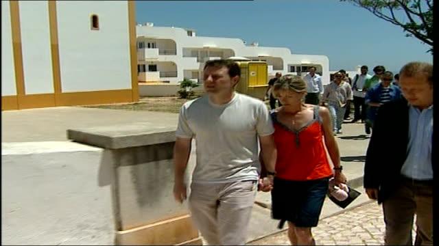 madeleine mccann abduction: police criticised; portugal: algarve: praia da luz: ext kate mccann and husband gerry mccann along away form church - マデリン・マクカーン失踪事件点の映像素材/bロール