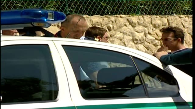 madeleine mccann abduction/ police search more properties; tx murat talking with police beside police car during search - fall madeleine mccann stock-videos und b-roll-filmmaterial