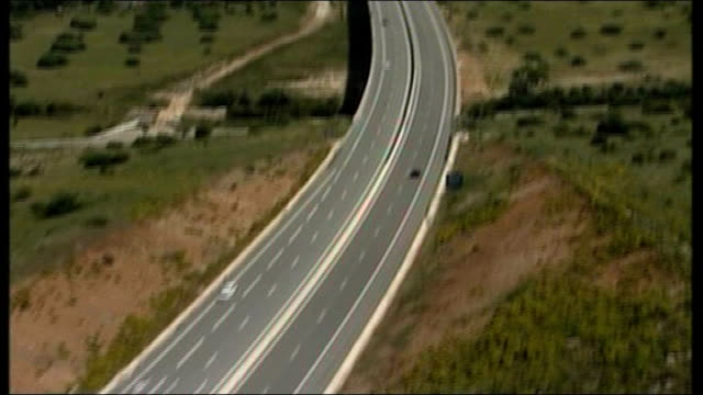 madeleine mccann abduction: spanish connection; portugal / spanish border: ext air views of highway and bridge into spain air view spanish harbour - マデリン・マクカーン失踪事件点の映像素材/bロール