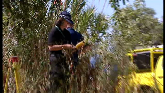 British police at search site **As incoming some distortion*** Various of police officers cutting down greenery at site and searching undergrowth /...