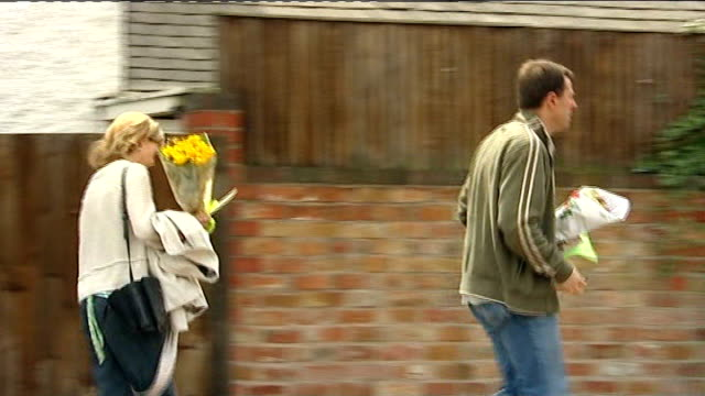 One year on Leicestershire Rothley EXT Gerry McCann and his wife Kate McCann towards and past holding bunches of flowers and holding hands Brian...