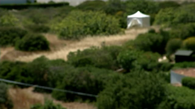 madeleine mccann disappearance: sniffer dogs used in renewed search effort; british and portuguese police at search site sutton with incident tent in... - disappearance of madeleine mccann stock videos & royalty-free footage