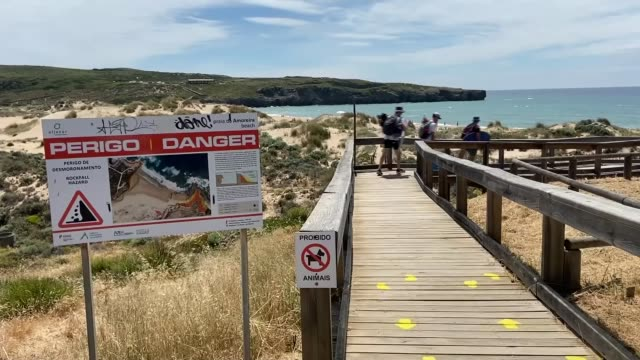 suspect also linked to disappearance of german boy in 1996 portugal algarve aljezur ext general views of beach sign 'perigo danger' waves crashing... - news not politics stock videos & royalty-free footage