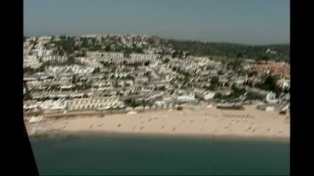 Picture of possible suspect released PORTUGAL Praia da Luz EXT AERIALs / AIR VIEWs of beach and town of Praia da Luz Man walking away down beach...