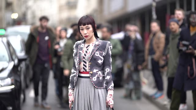 Mademoiselle Yulia wears a gray pleated skirt socks black shoes a jacket with embroidery outside Thom Browne during Paris Fashion Week Womenswear...