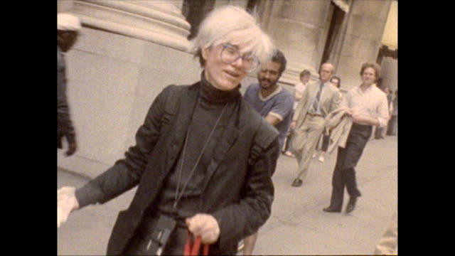 Madison Avenue walking by B Dalton department store Warhol accompanied by director Russ Karel and a young woman walks his dog on a leash cleans up...
