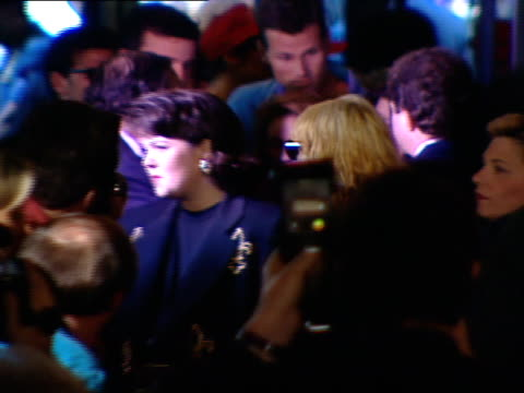 Madonna actress Rosie O'Donnell entering crowded Ziegfeld movie theatre posing for press photographs walking w/ security into theatre lobby agent...